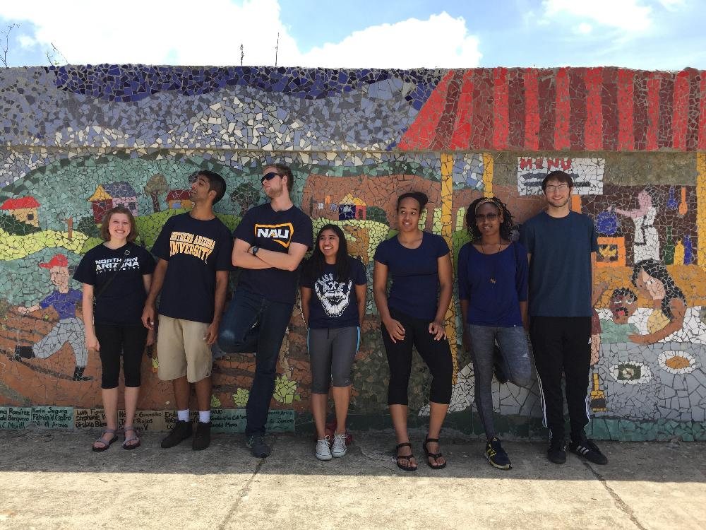 Several students leaning against a colorful mural