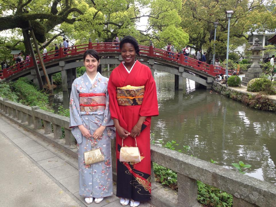 Students in traditional Japanese wear in front of a bridge