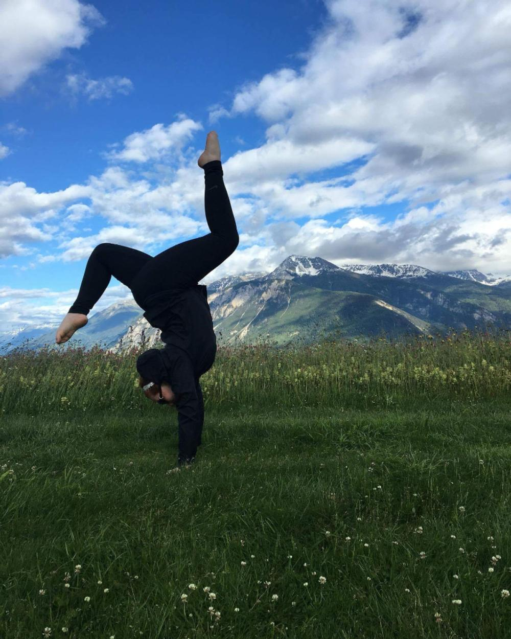 Student doing a handstand in a field with a mountain in the background